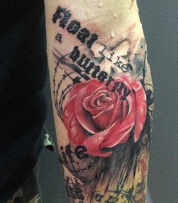 手臂鲜红的花朵和字母纹身